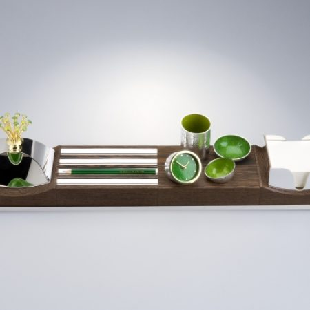 Contour Material: Silver, wenge and enamel  Dimensions: 130 mm x 630 mm x 130 mm  Consisting of four elements Contour includes a blotter, a paper holder, pen holders, a clock and small bowls for stationary items. The piece is contained in a silver tray and both the wood and silver can all be moved around as the viewer desires.  The Silver Trust Collection at Downing Street.